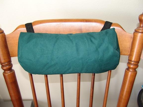 green fiber filled pillow on rocking chair