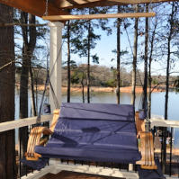 Loveseat Lounger hanging from porch at lake.